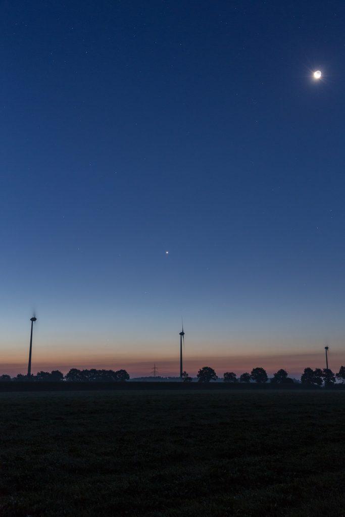 Von oben rechts nach unten links: Mond mit Erdschein, Venus, Merkur und Mars um 5:51 Uhr MESZ. Die letzten beiden stehen direkt am Horizont mittig zwischen den beiden Windrädern. (Bild: B. Knispel)