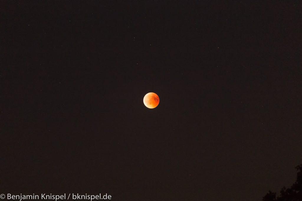Noch total verfinsterter Mond kurz vor dem Ende der Totalität im umgebenden Sternenfeld. (Bild: B. Knispel)
